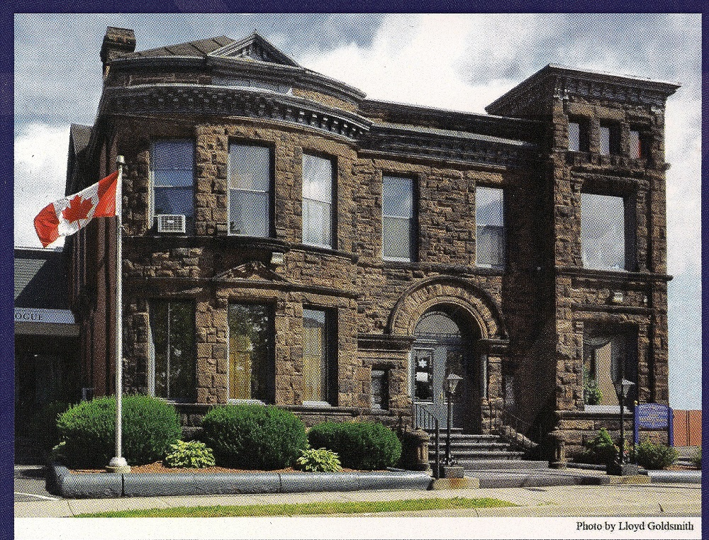 Large sandstone two story building with large windows, entrance with stairs and Canada flag on pole at left