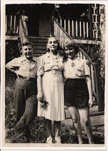 Woman standing at bottom of wooden steps leading to cottage with teenaged daughter on her left arm and teenaged son at her right arm