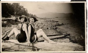 Two women in bathing suits seated on a large piece of driftwood on a beach with their backs together