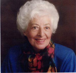 Portrait officiel d'une femme aux cheveux blancs portant un vêtement bleu et un foulard multicolore.