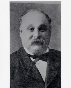 Formal black and white portrait of man with receding hairline and mustache