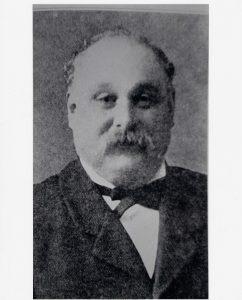Portrait officiel en noir et blanc d'un homme au crâne dégarni portant une moustache.
