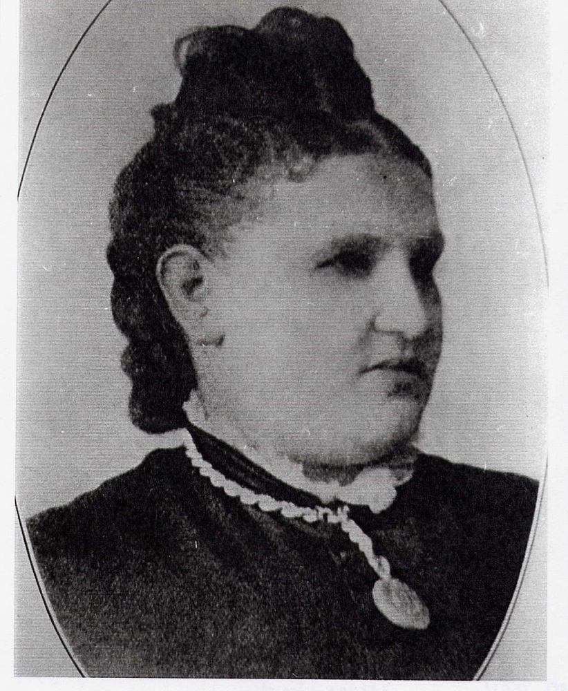 Formal black and white portrait of woman with lace collar and pendant