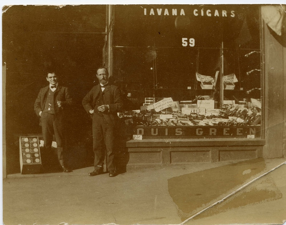 """Storefront with large glass window with """"Havana Cigars"""" written at top of window and """"Louis Green"""" printed at bottom – the window displays cigars and tobacco products – two men standing in doorway"""