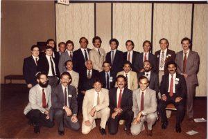 Vingt-trois hommes portant veston-cravate disposés en trois rangées.