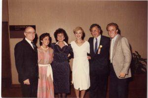 Trois hommes et trois femmes, les hommes en veston-cravate et les femmes en robe, se tenant bras dessus, bras dessous.