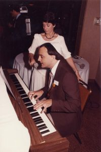 Man seated at piano with woman holding a microphone to his mouth
