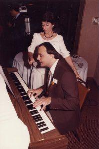 Homme au piano et femme debout à côté de lui, tenant un micro.