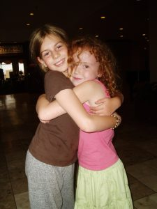 Two girls with arms wrapped around each other