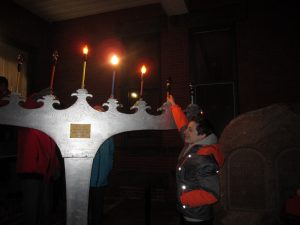 Large grey painted Chanukah menorah with some candles lit and teenaged boy reaching up to adjust lights