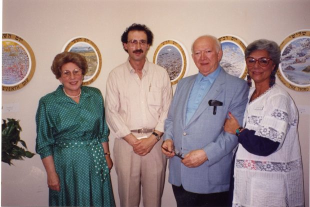 Two men and two women standing together – paintings on wall in background
