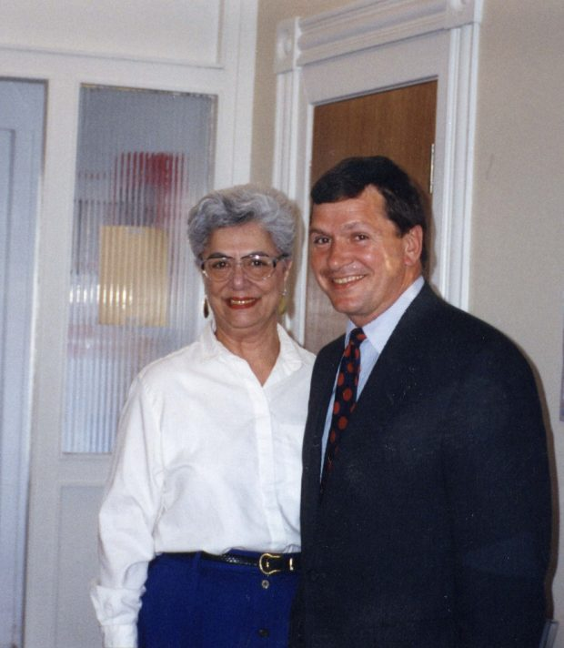Grey haired woman in white blouse and man in dark business suit – smiling toward camera