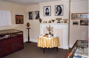 Exhibition room in Museum with two display cabinets, table set for Sabbath meal, assortment of brass Chanukah menorahs on mantelpiece and photographs on wall