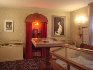 Arrangement d'exposition au Musée : trois présentoirs vitrés, une arche sainte en bois et, à droite, le portrait d'un homme en prière peint par Fred Ross.