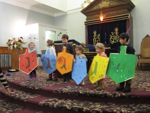 Six children standing on platform at front of Synagogue – each child holding a life-size colourful cardboard dreidl