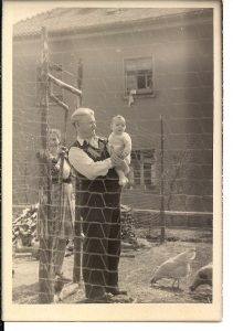 Man with white hair holding infant son in his arms and wife in background – all are posing behind a barbed wire fence