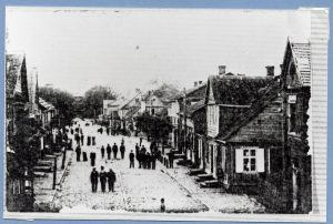 Unpaved village street with small two story wooden buildings on either side and several men walking or gathered in street
