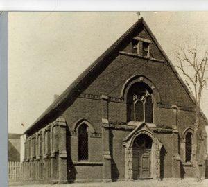 Immeuble en pierre comportant une toiture à double pente ainsi qu'une porte et des fenêtres surmontées d'arcs arrondis.