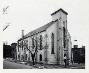 Édifice en brique de style néo-gothique de l'apogée victorien présentant des fenêtres en arc et une colonne centrale autrefois surmontée d'une flèche de clocher.
