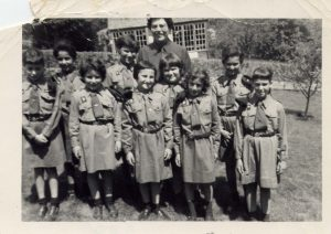 9 girls in Brownie uniform dresses with leader in Brownie uniform standing behind