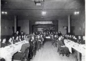 Women seated at long tables with one table as the head table in the background.