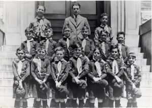14 boys in Cub uniforms with hats in hand standing in two rows on stairs with leaders in third row behind