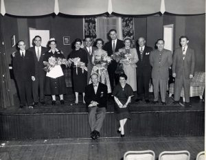 11 men and women in costumes standing at front of stage with man and woman seated on stage edge in front of them