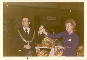 Colour photograph showing man in business with mayoral chain of office and woman standing in front of baking table at Hadassah Bazaar