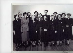 14 middle aged women in skirts and jackets standing in two rows