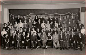 Soixante-dix jeunes hommes et femmes en tenue de soirée disposés en quatre rangées.