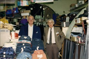 Two men in suit jackets standing behind counter with display of men's work shirts and crowded shelves to the right