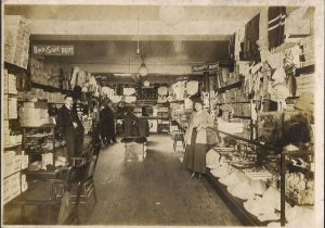 View inside a narrow dry goods shop with counters and shelves with boxes on either side and at the back, man at left, woman at right