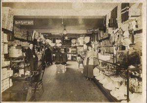Vue à l'intérieur d'un étroit magasin d'articles de mercerie dont les comptoirs et rayons sont remplis de boîtes, d'un côté comme de l'autre. Un homme se tient à gauche et une femme à droite.