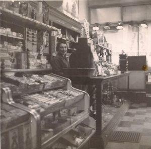 Photographie montrant l'intérieur d'un magasin dont le comptoir regorge de petits articles et dont les rayons sont remplis de boîtes. Une jeune femme se tient derrière une grosse caisse enregistreuse posée sur le comptoir.