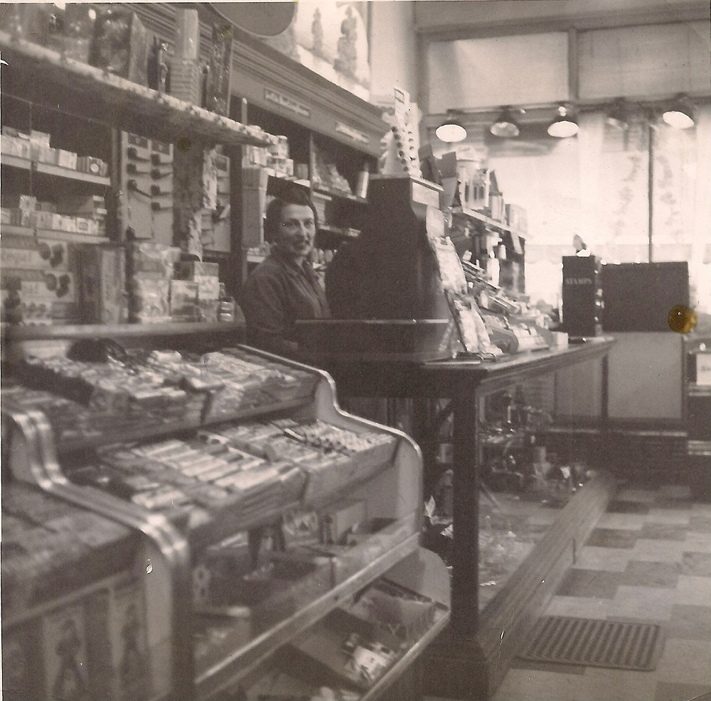 View shows interior of store with counter hilding small items, shelves with boxes and young woman at counter beside large cash register
