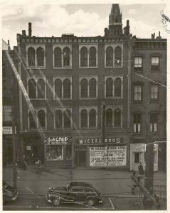 Immeuble de quatre niveaux comprenant 12 paires de fenêtres doubles aux étages et des enseignes au rez-de-chaussée pour les magasins « Jack Calp The Men's Shop » et « Wiezel Bros ».