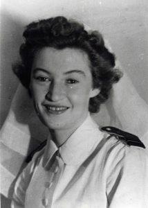 Portrait officiel d'une jeune femme portant le voile blanc et l'uniforme blanc des infirmières militaires.