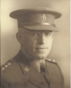 Formal portrait of man with wire framed glasses and wearing uniform of Canadian Army with pin for Canadian Dental Corps