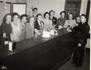 10 women lined up behind long counter, some wearing aprons – two men in naval uniforms at far end