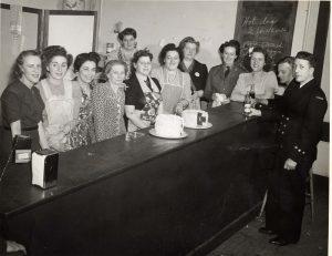 Dix femmes alignées derrière un long comptoir, certaines portant un tablier, et deux hommes portant des uniformes de la marine au bout du comptoir.