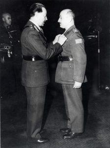 Deux hommes en uniforme de l'Armée canadienne, celui de droite recevant une médaille de la part de celui de gauche.