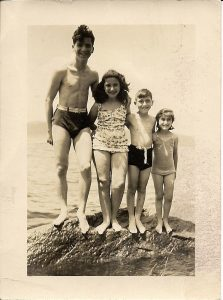 Four children in bathing suits standing on a rock – arranged from left from tallest and oldest to youngest and shortest