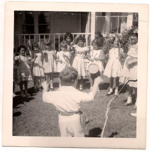 Boy standing with back to camera directing group of girls wearing summer dresses and holding assorted instruments including triangles and tambourines