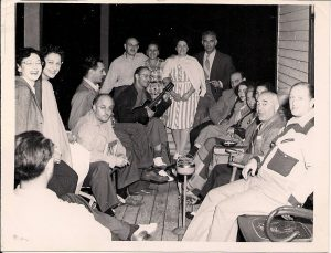 16 men and women seated on a wooden verandah – one man holding a ukelele