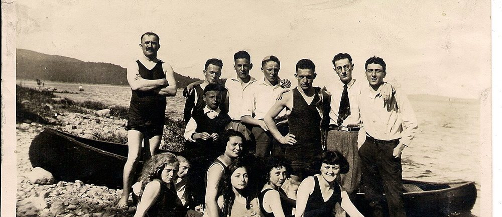 13 friends – some in bathing suits, others in pants and shirts gathered in front of a beached canoe