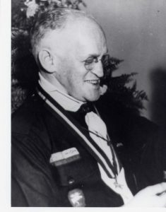 Portrait d'un homme, de profil, portant un uniforme de chef des scouts.