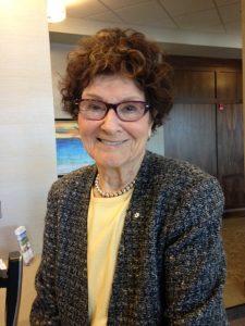 Portrait officiel d'une femme aux cheveux châtains portant des lunettes et une veste en tweed.