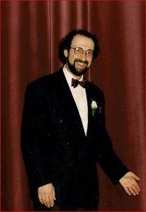 Homme portant des lunettes, une barbe et un smoking.