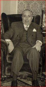 Man wearing a three piece suit and glasses seated in a wingback chair