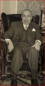 Homme assis dans un fauteuil bergère à oreilles portant un complet avec gilet et des lunettes.